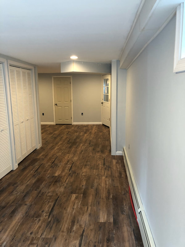 Basement renovation with dark wood floors, blue walls and new white closet folding doors