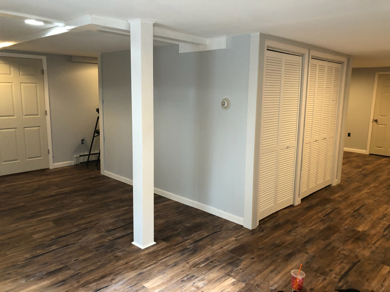Basement renovation with gray blue walls, folding closet doors and column covering