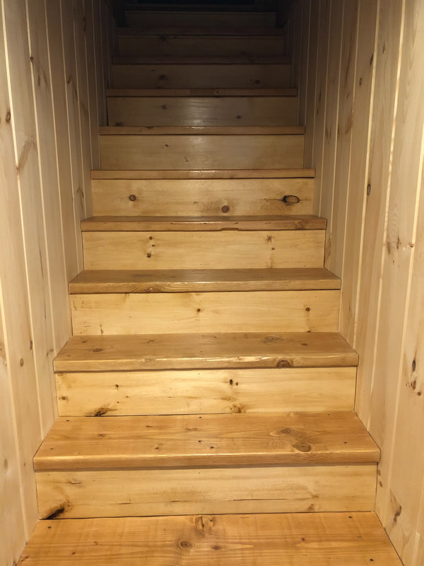 Custom carpentry basement stairwell and wood paneling along walls