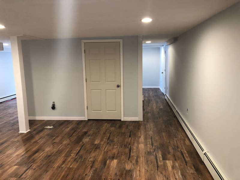 Basement renovation with new wood floors and fresh paint